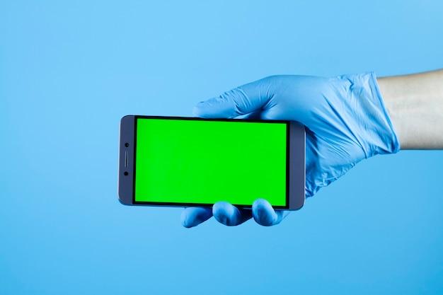 Mężczyzna ręka trzyma telefon w ochronnej rękawicy medycznej, wirus koronawirusa covid-19