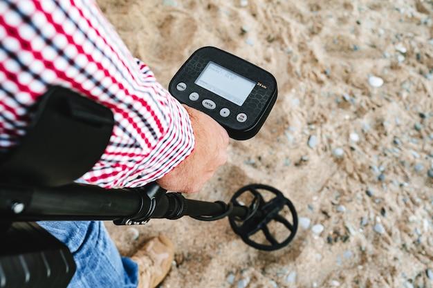 Mężczyzna ręka trzyma urządzenie wykrywające metal nad ziemią z bliska