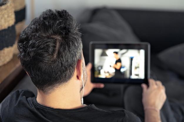 Mężczyzna ręka trzyma za pomocą cyfrowego tabletu oglądając lekcje mistrzowskie online. uczenie się zdalnie.
