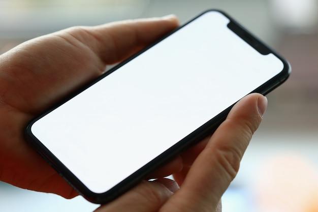 Mężczyzna ręka trzymać nowoczesny smartfon z pustym ekranem