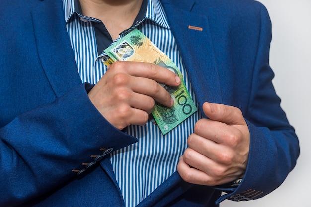 Mężczyzna ręka ukrywa do kieszeni banknoty dolara australijskiego