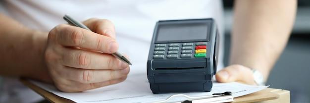 Mężczyzna ręka znak odbioru zamówienia z bliska. dostawa towaru kurierem i płatność przelewem. koncepcja terminala, kartonu i dokumentu.