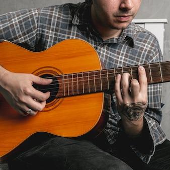 Mężczyzna ręki bawić się gitarę akustyczną