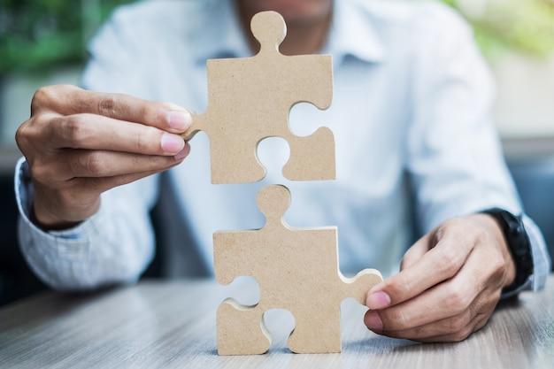 Mężczyzna ręki łączy pary łamigłówkę nad stołem, biznesmen trzyma drewnianą wyrzynarkę wśrodku biura. rozwiązania biznesowe, misja, cel, sukces, cele i strategie