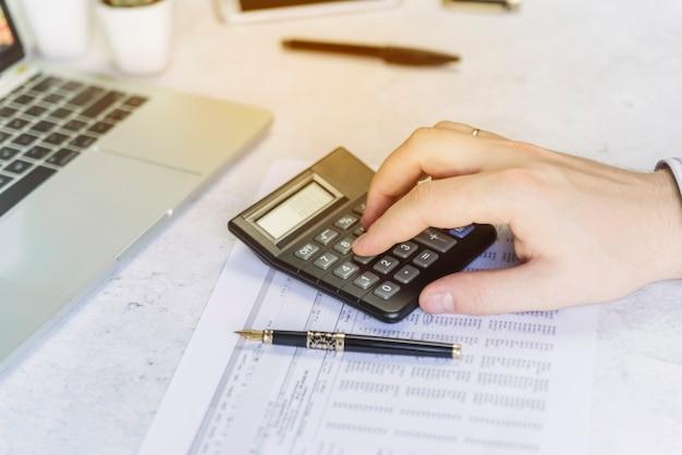 Mężczyzna ręki liczenie na kalkulatorze