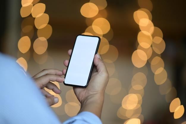 Mężczyzna ręki mienia mobilny smartphone z plamy bokeh tłem