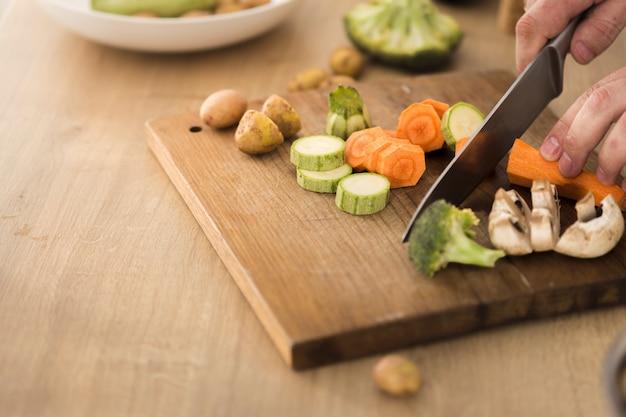 Mężczyzna ręki pokrajać warzywa dla gotować jarskiego zdrowego jedzenie gotuje w domu pojęcie