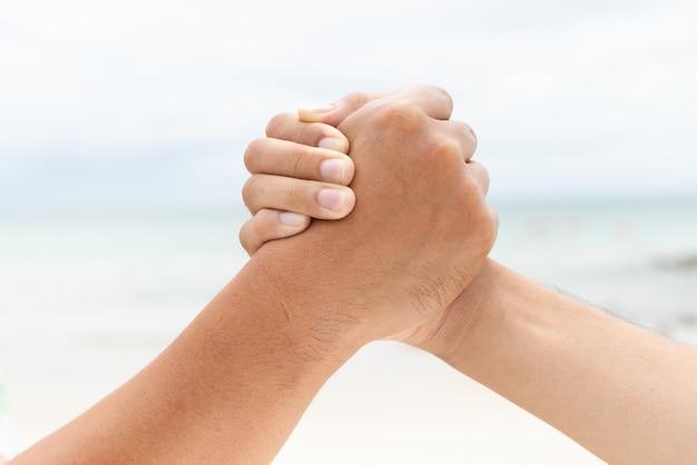 Mężczyzna ręki potrząśnięcie trzyma wraz z nieba tłem