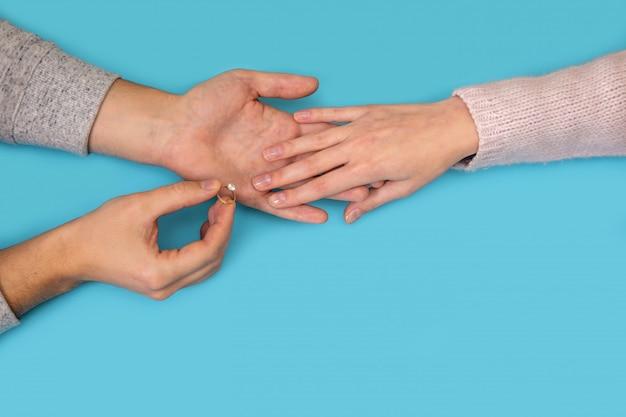 Mężczyzna ręki trzyma obrączkę ślubną blisko kobiety ręki na błękicie.