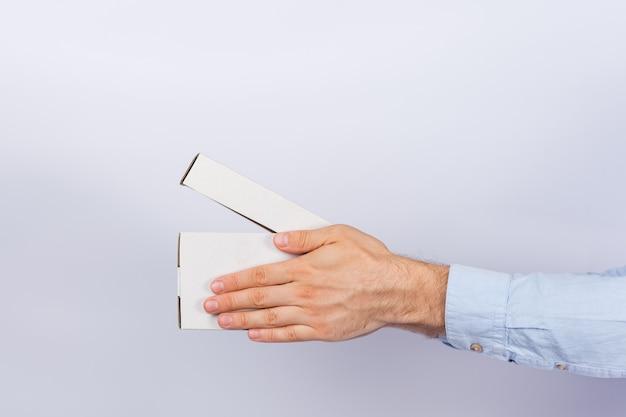 Mężczyzna ręki trzyma otwartego pudełko na białym tle. bezpieczna dostawa paczek. widok z boku