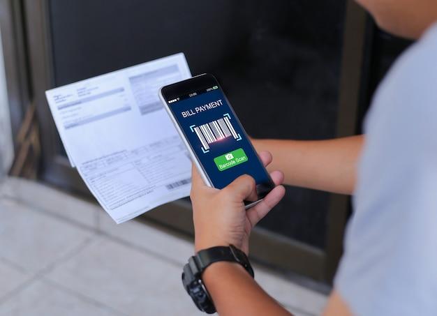 Mężczyzna ręki używać telefon komórkowego i trzymający rachunki