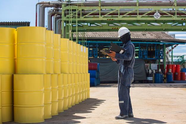 Mężczyzna rekord inspekcji pracownika bębna beczki zapasów ropy żółty pionowe lub chemiczne dla w branży.