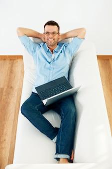 Mężczyzna relaksujący na kanapie z laptopem i ręką za głową