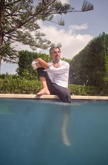 Mężczyzna relaksuje się przy basenie latem?