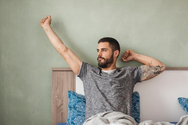 Mężczyzna relaksuje w jego łóżku