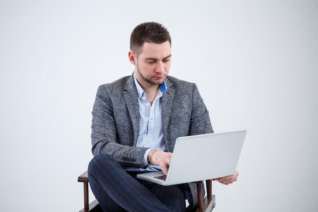 Mężczyzna reżyser dyrektor biznesmen siedzi na krześle studiując dokumenty. patrzy na ekran laptopa. nowy projekt biznesowy.