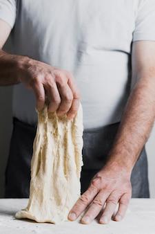 Mężczyzna robi ciastu dla chlebowego frontowego widoku
