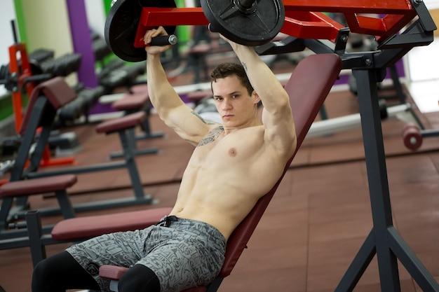 Mężczyzna robi ćwiczenia klatki piersiowej na pionowej maszynie do wyciskania na ławce