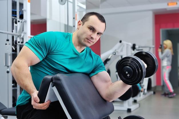 Mężczyzna robi ćwiczenie bicepsa na ławce scott z hantlami