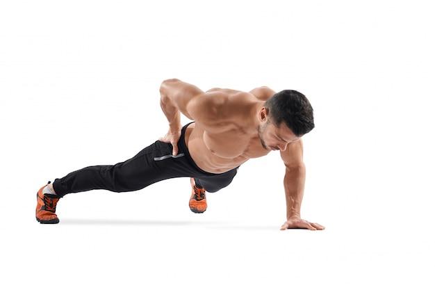 Mężczyzna robi deski ćwiczeniu z jednej strony.