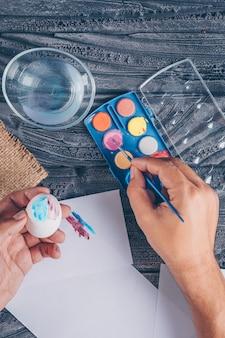 Mężczyzna robi easter egg z farbą na ciemnym drewnianym tle