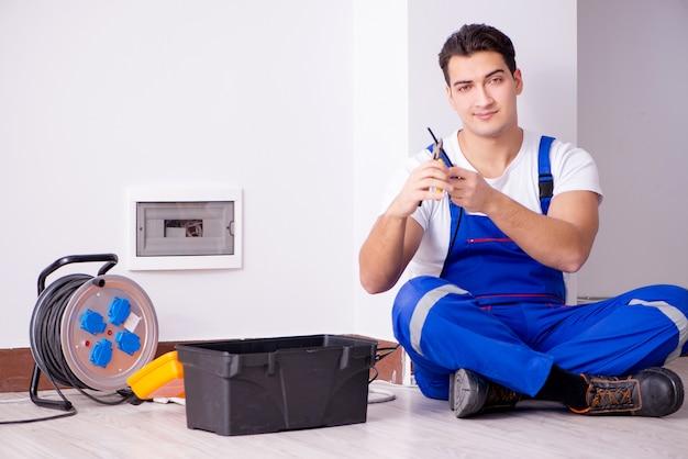 Mężczyzna robi elektrycznym naprawom w domu