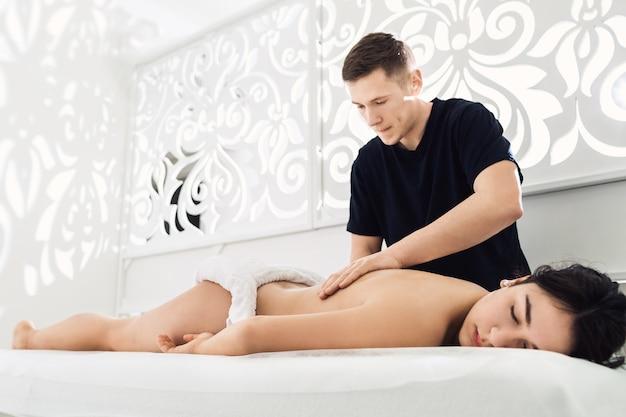 Mężczyzna robi masaż pleców do pięknej młodej kobiety w spa.
