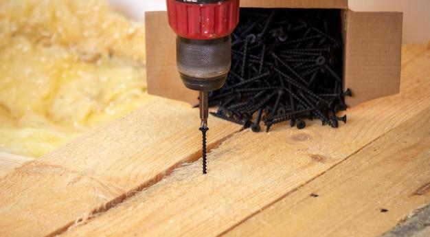 Mężczyzna robi naprawy w domu, śrubokręt, śrubki, piła. drewniana podłoga. selektywne skupienie