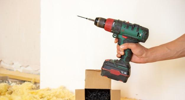 Mężczyzna robi naprawy w domu, śrubokręt, śrubki, piła. drewniana podłoga.