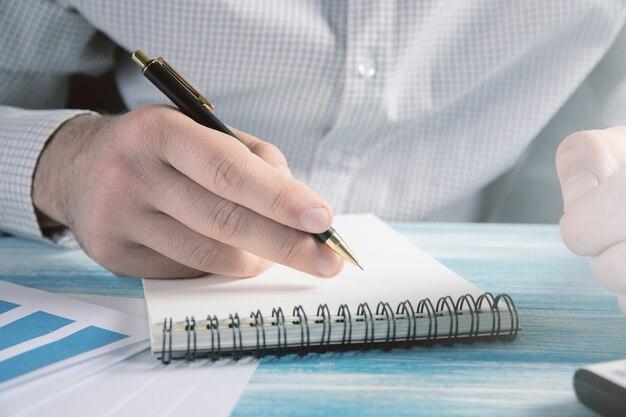 Mężczyzna robi notatki na notebooku