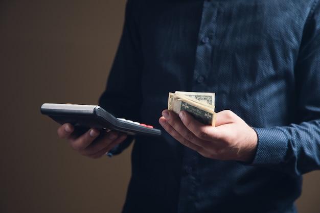 Mężczyzna robi obliczenia na lodówce i trzyma pieniądze na brązowej powierzchni