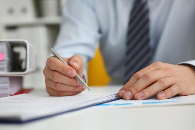 Mężczyzna robi papierkową robotę w biurze za pomocą pióra