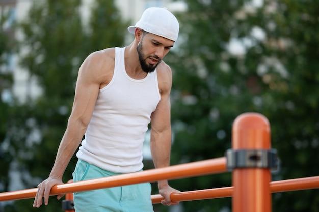 Mężczyzna robi pompki na barach na ulicy w dzień