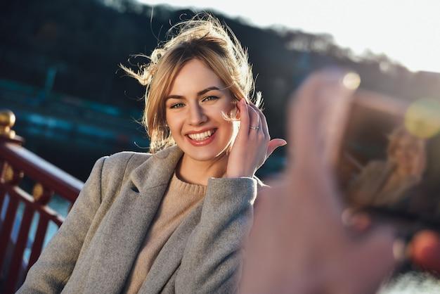 Mężczyzna robi portret szczęśliwej uśmiechniętej kobiety stojącej na moście w słoneczny letni lub wiosenny dzień na świeżym powietrzu