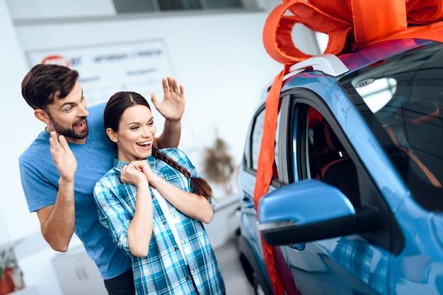 Mężczyzna robi prezent - samochód dla swojej żony.