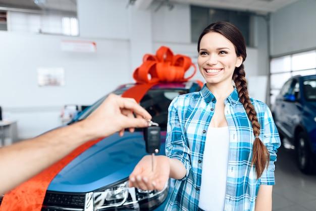 Mężczyzna robi prezent - samochód swojej żonie. jest tym zaskoczona