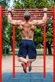 Mężczyzna robi pull-up na poziomym pasku