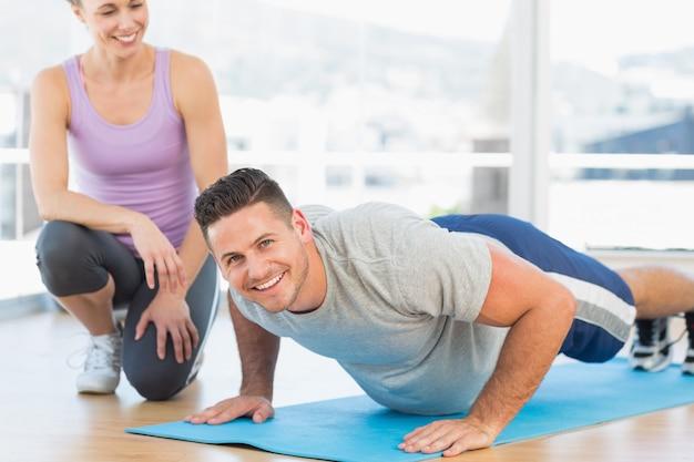 Mężczyzna robi push up z żeńskim trenerem