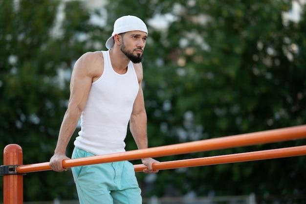 Mężczyzna robi push-upy na barach na ulicy w ciągu dnia