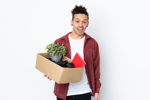 Mężczyzna robi ruch, podnosząc pudełko pełne rzeczy na białym tle z zaskoczeniem i zszokowanym wyrazem twarzy