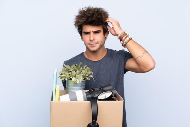 Mężczyzna robi ruch, podnosząc pudełko pełne rzeczy niezadowolonych i sfrustrowanych czymś. negatywny wyraz twarzy