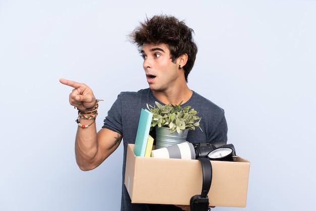 Mężczyzna robi ruch, podnosząc pudełko pełne rzeczy, wskazując palcem na bok