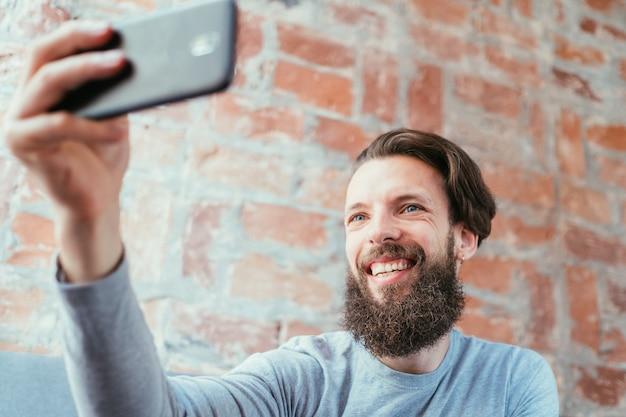 Mężczyzna robi selfie i trendy społeczne. fotografia mobilna. bezczynny wypoczynek i próżność.