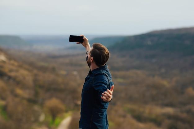 Mężczyzna robi selfie w górach