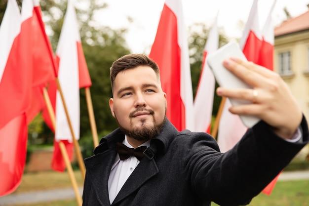 Mężczyzna robi selfie z flagami polski z tyłu