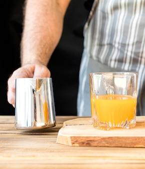 Mężczyzna robi sokowi pomarańczowemu