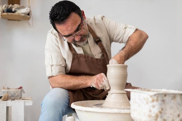 Mężczyzna robi średni strzał z ceramiki