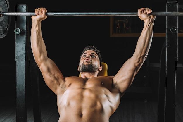 Mężczyzna robi wyciskanie na ławce z ciężarami na siłowni