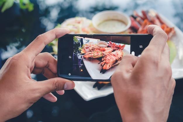 Mężczyzna robi zdjęcia jedzeniem na stole ze smartfonem do udostępniania w mediach społecznościowych