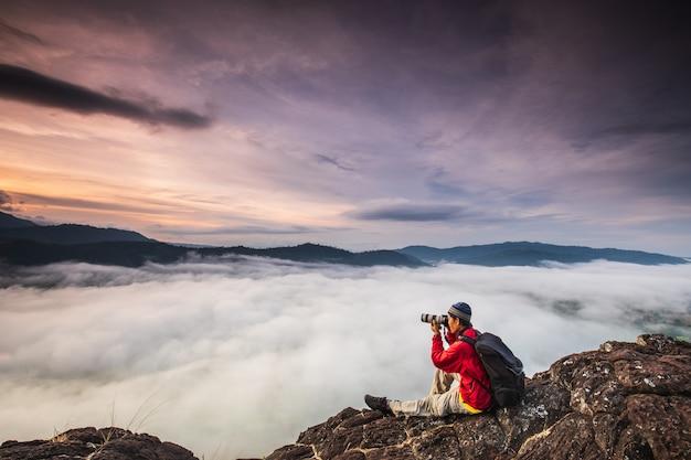 Mężczyzna robi zdjęcia morza mgły na wysokiej górze.